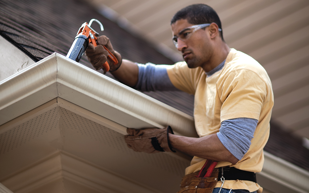 A person adding plastic roofing cement around white gutters on a roof's edge.
