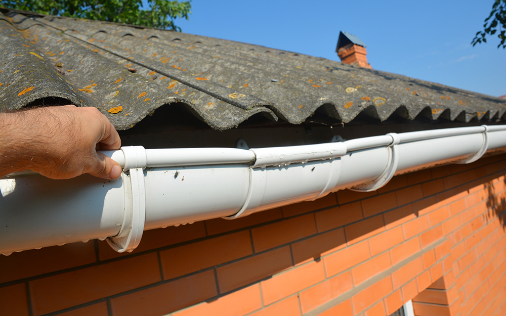 A person applying silicone to seal part of a gutter system.