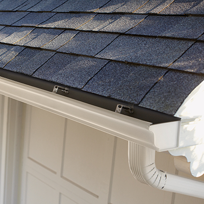 A close-up view of white gutters on the edge of a home roof.