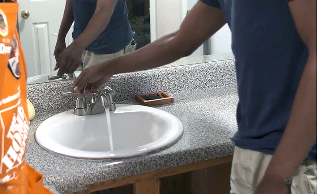 A person tests a new bathroom faucet by running the water.