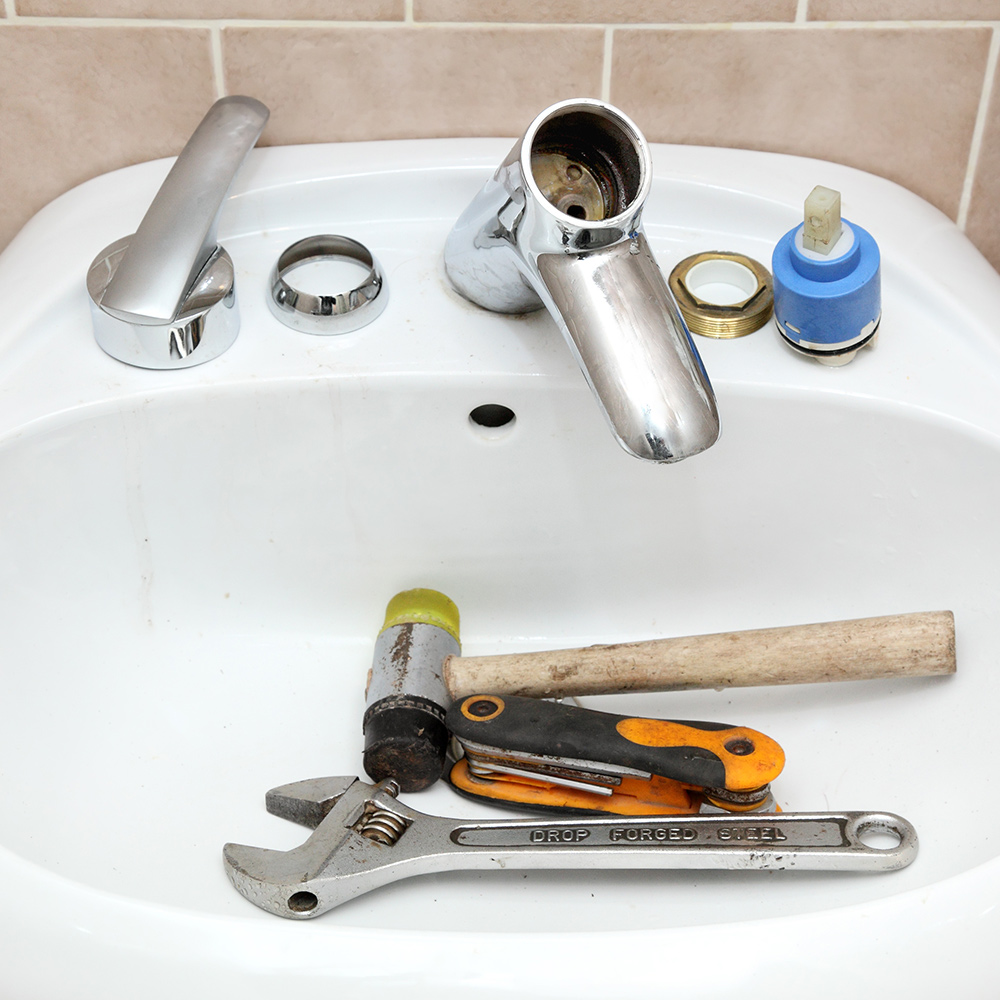 A bathroom cartridge faucet is disassembled with tools in the sink.