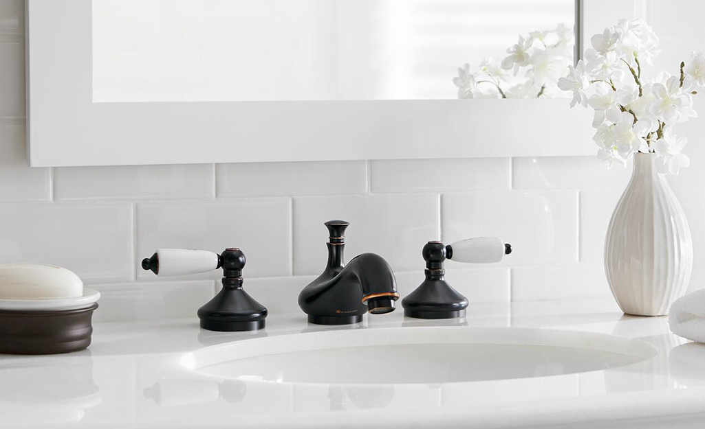 A two-handled bathroom sink has a cartridge faucet.