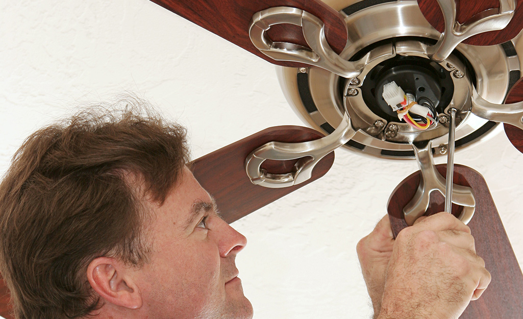 a man unscrewing a part of a ceiling fan