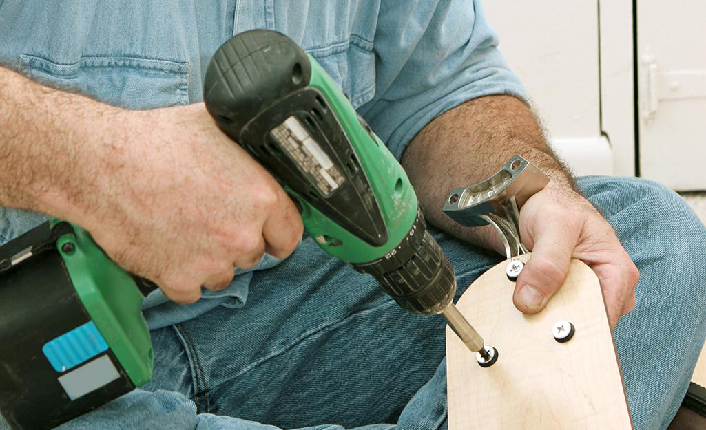 a man installing screws on a new ceiling fan blade