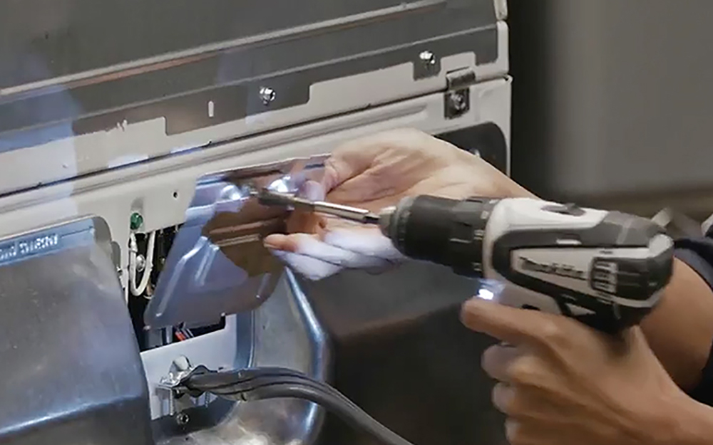 person using a drill to open a dryer access panel
