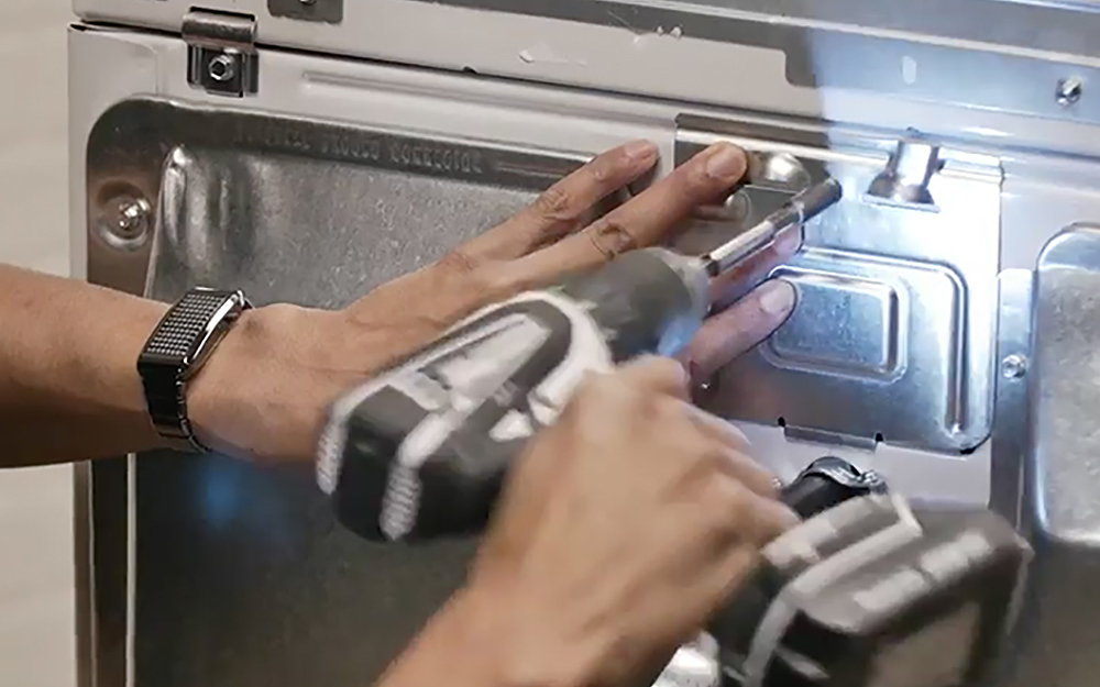 Person installing back panel on a dryer.