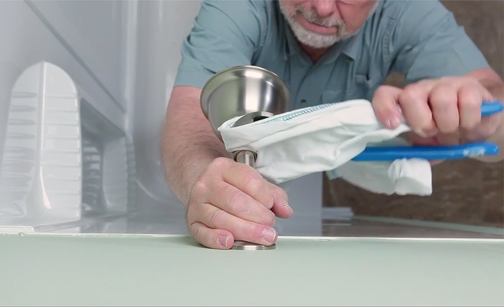 A man removing the old trim on his shower faucet.