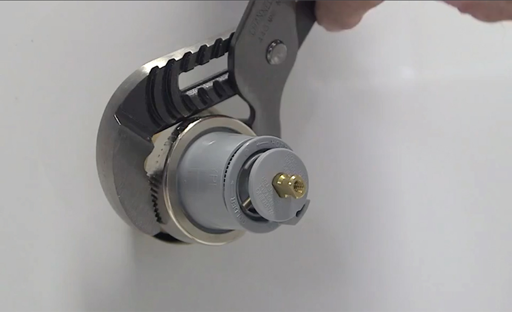 A person uses a wrench to install a cartridge.