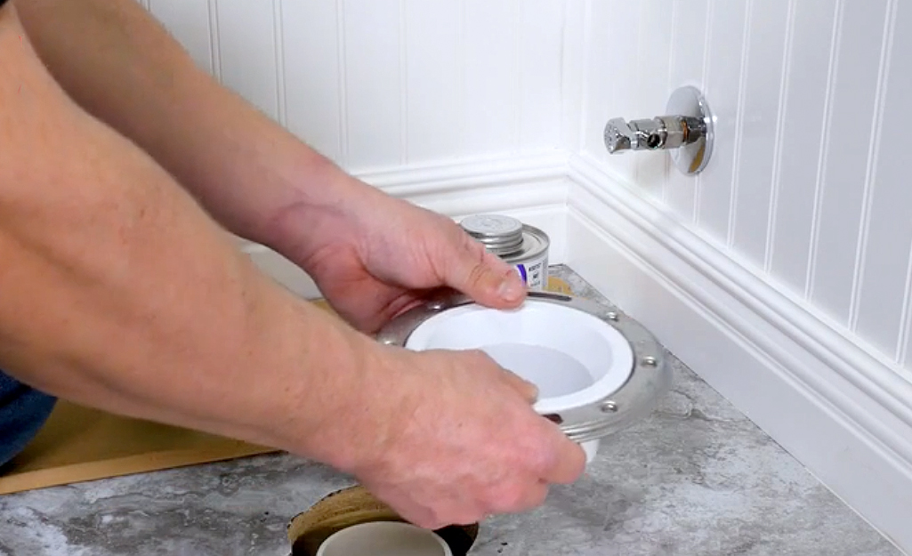 A person holding a new toilet flange over a drain pipe.