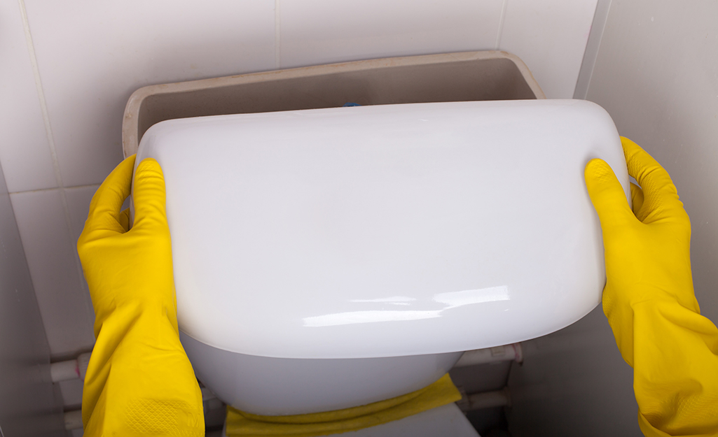 A person wearing rubber gloves removing a toilet tank lid.