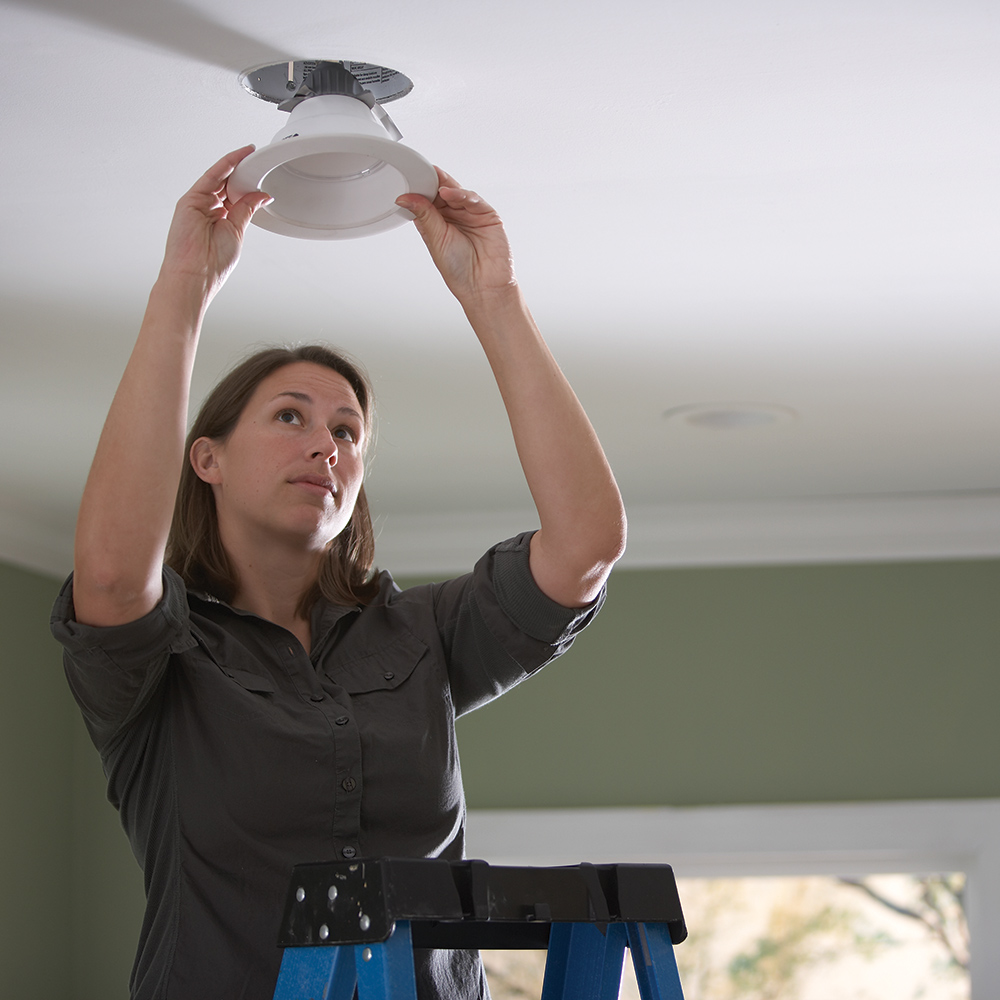 A woman standing on a ladder replaces a recessed lighting fixture in the ceiling.