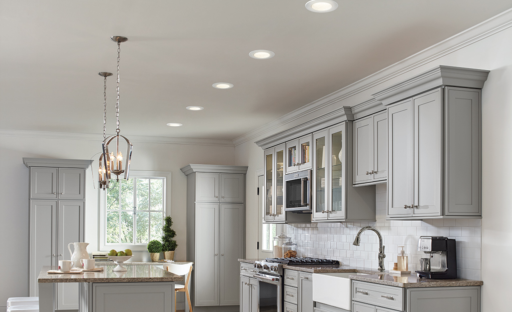 A row of recessed lights shines down into a kitchen with gray cabinets and an island.