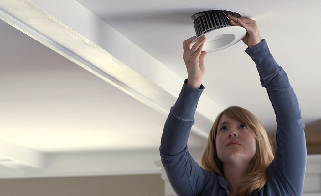 A woman reaches up to take a recessed lighting fixture out of the ceiling.