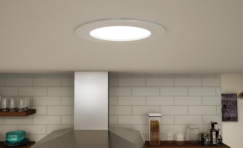 recessed light shines down onto the hood of an oven and a subway tile wall.