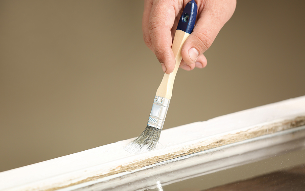 A person paints a wood window frame with white paint.