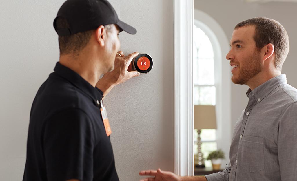 Một nhân viên Home Depot đứng cạnh chủ nhà và điều chỉnh bộ điều nhiệt thông minh trên tường.