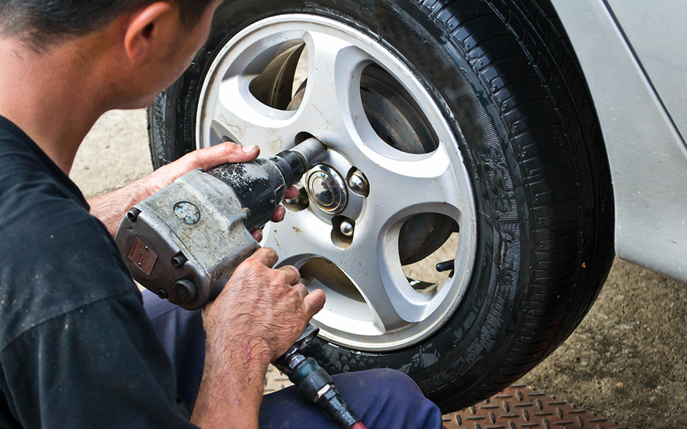 A person tightening lug nuts with a pneumatic wrench.