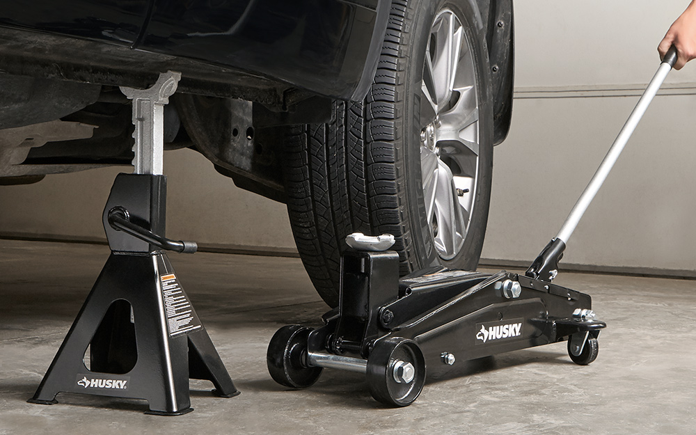 A jack stand supporting a car by the frame as a floor jack is moved out of position.