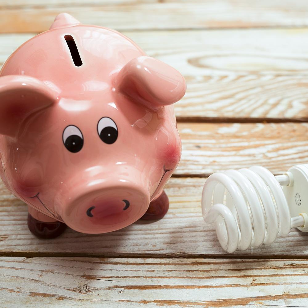 A piggy bank sits on a table near an LED bulb.