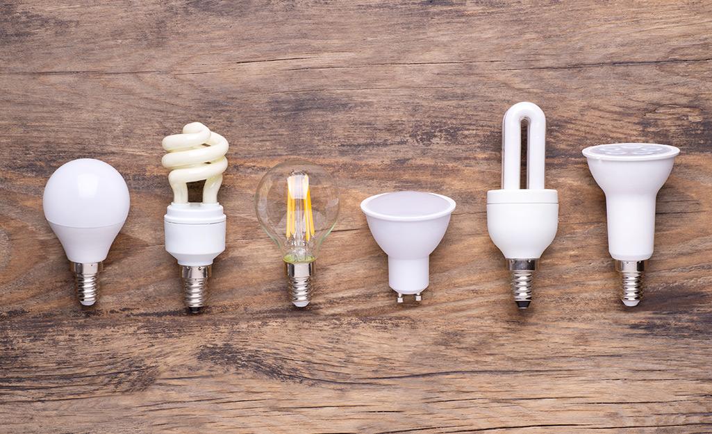 Six various energy-saving bulbs sit on a table.