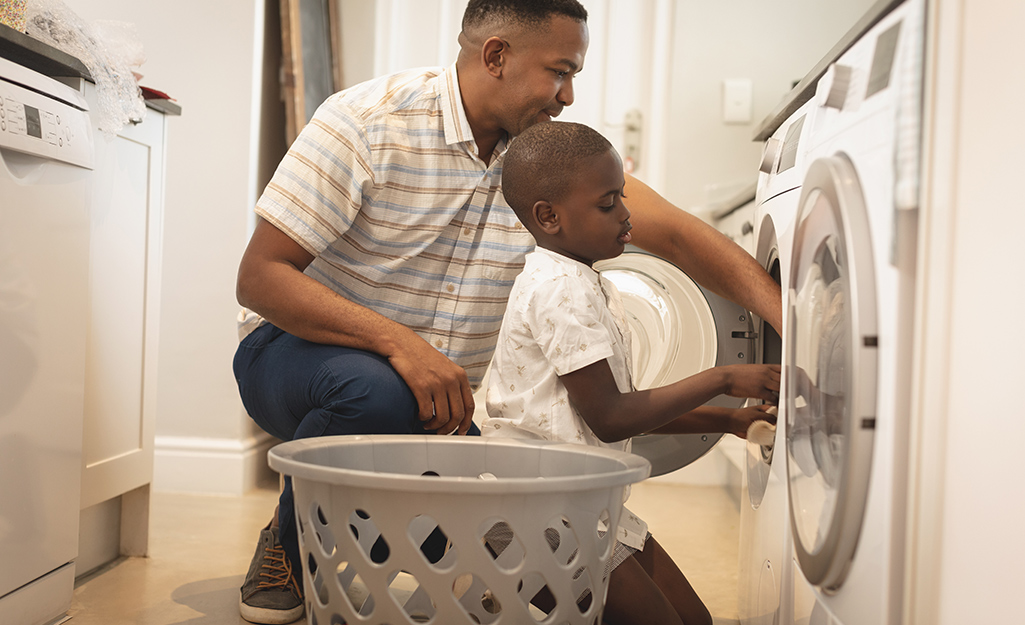 A father and son take laundry out of a dryer.