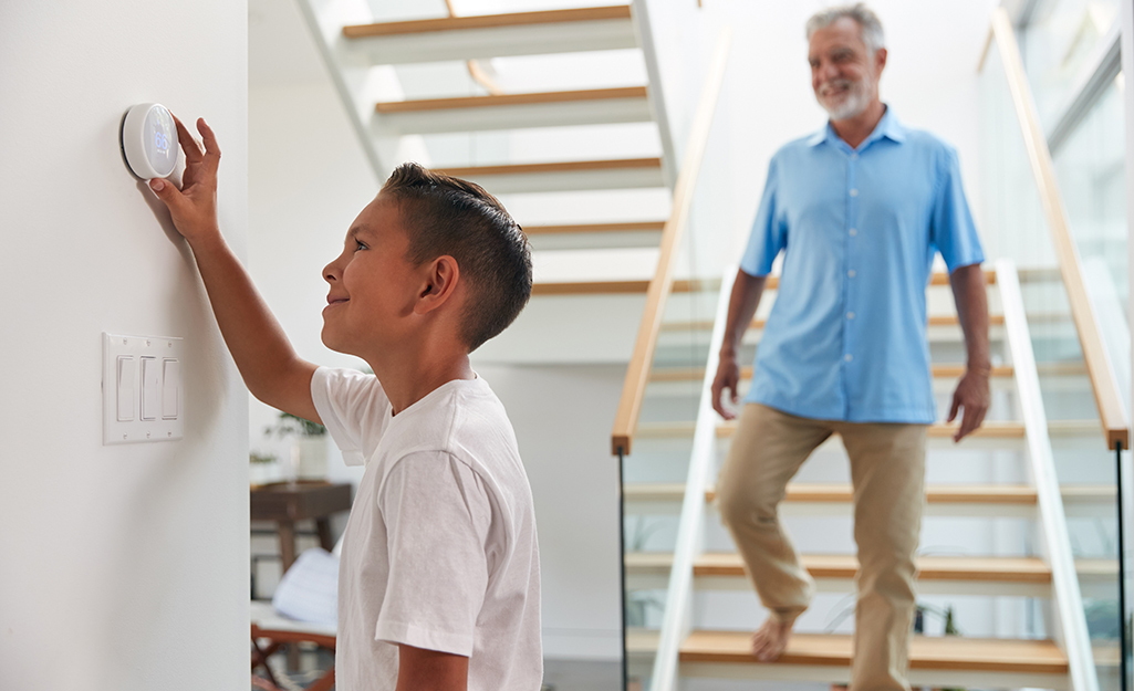 A father watches his young son use a thermostat.