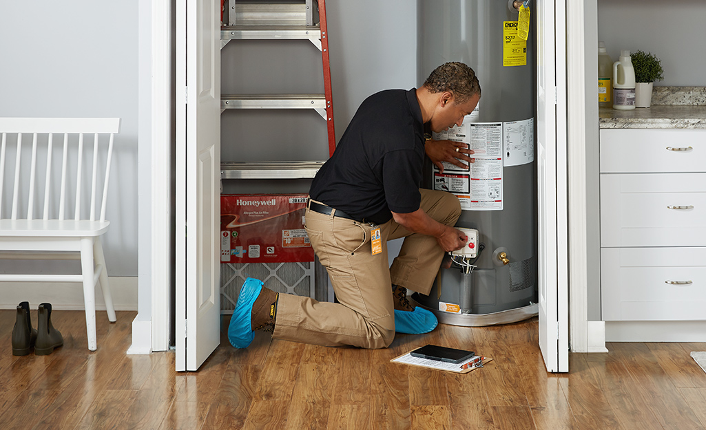 A man inspecting a water heater inside a home.