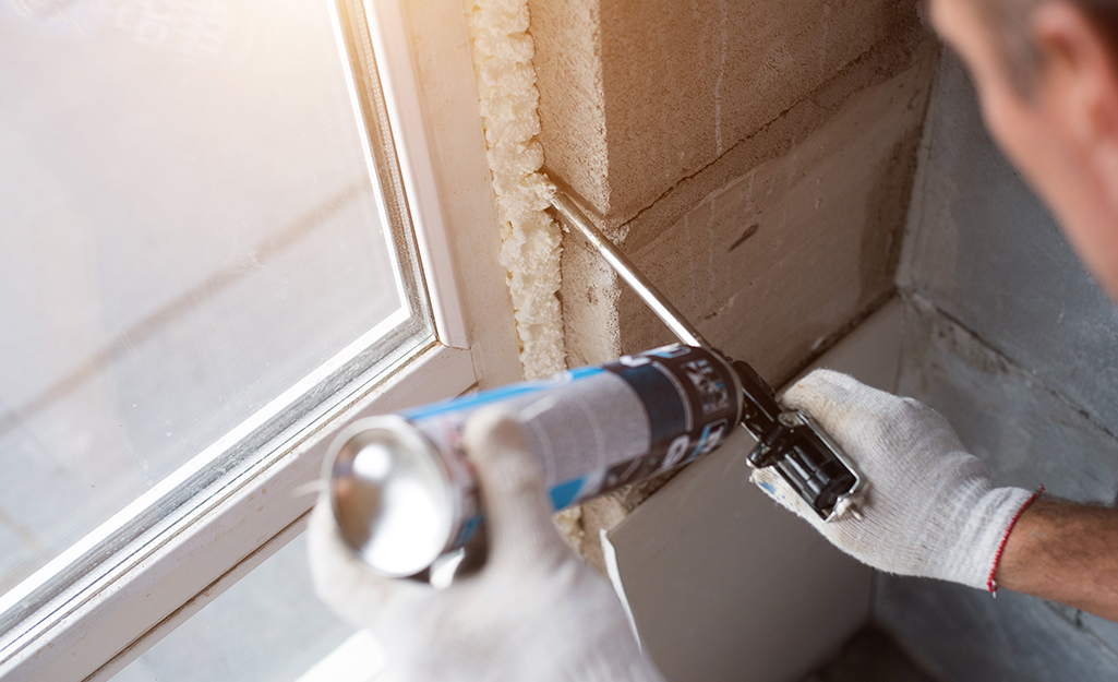 A man uses caulk to insulate windows.