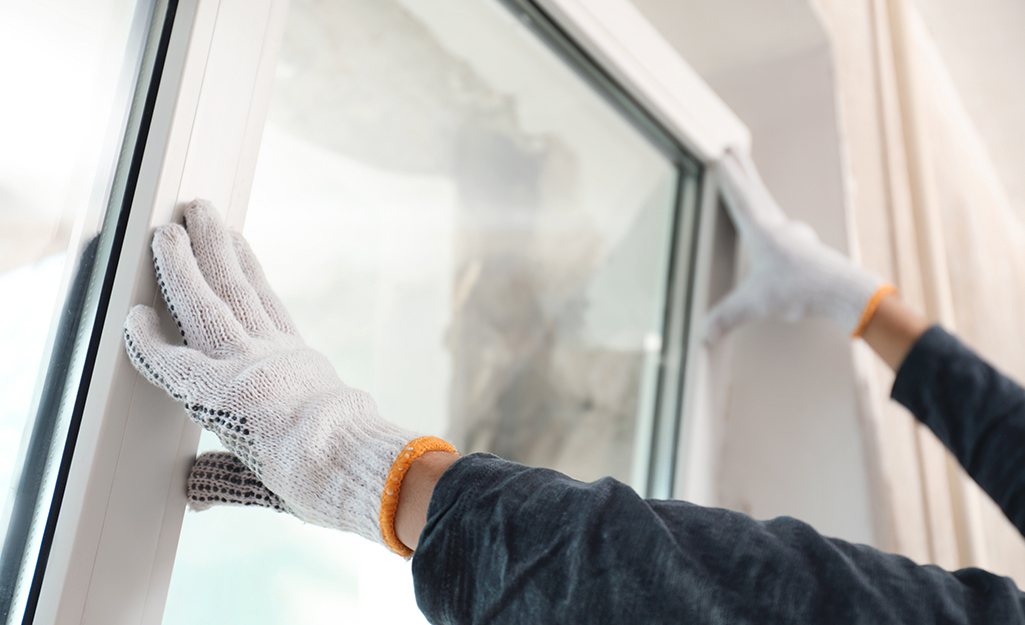 A person wearing safety gloves installs a window.