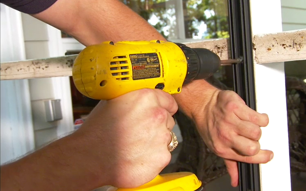 A person using a power drill to fasten a base strip to porch framework.
