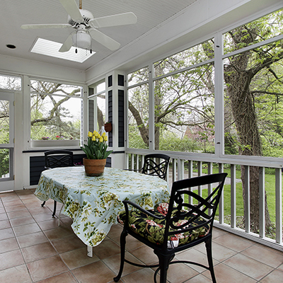 A screened-in porch surrounds a patio table with chairs.