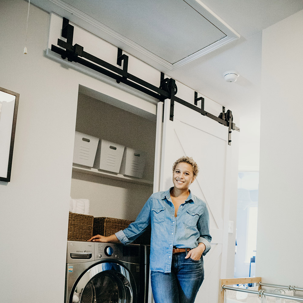 A woman standing in front of a laundry room with a barn door.