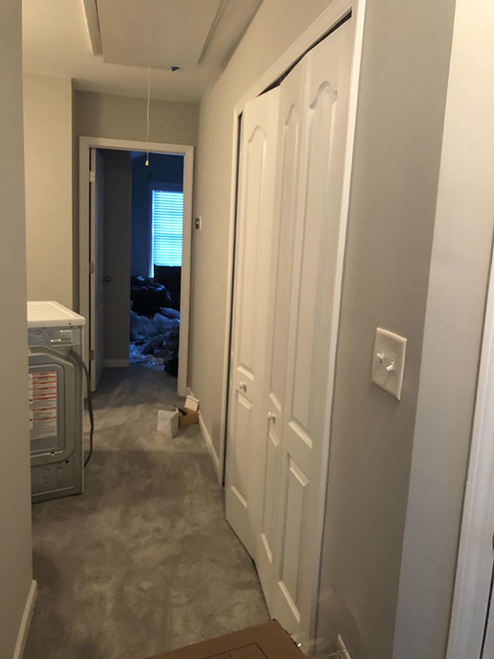 A washing machine sitting in a carpeted hallway.