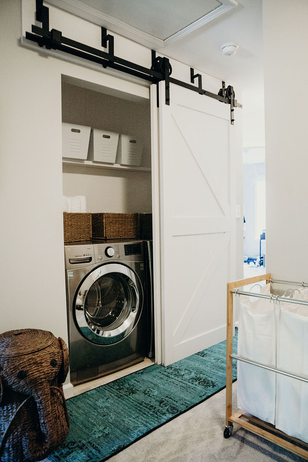 A laundry room closet with a front load washing machine.