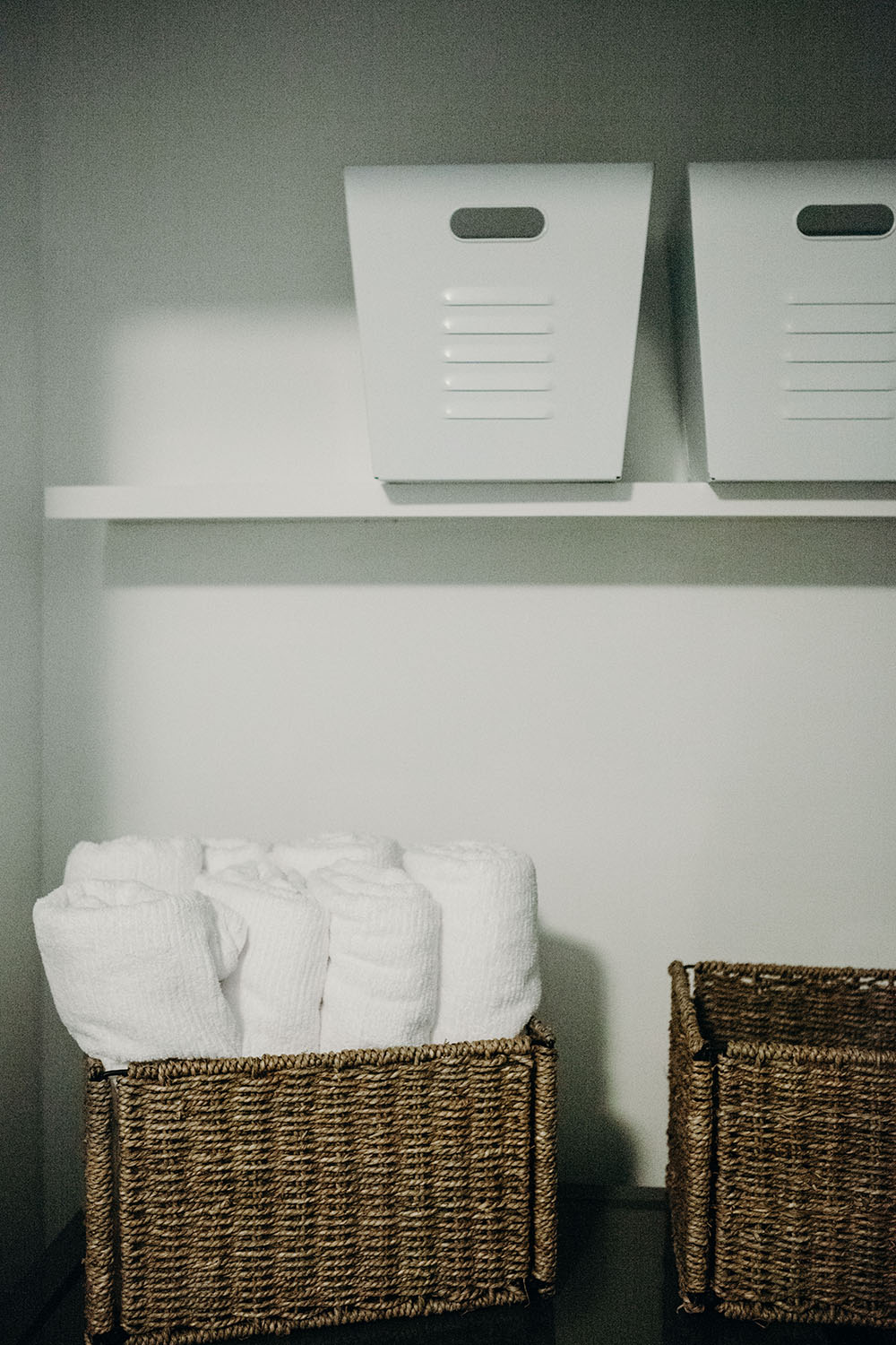 A pair of floating shelves decorated with storage bins.