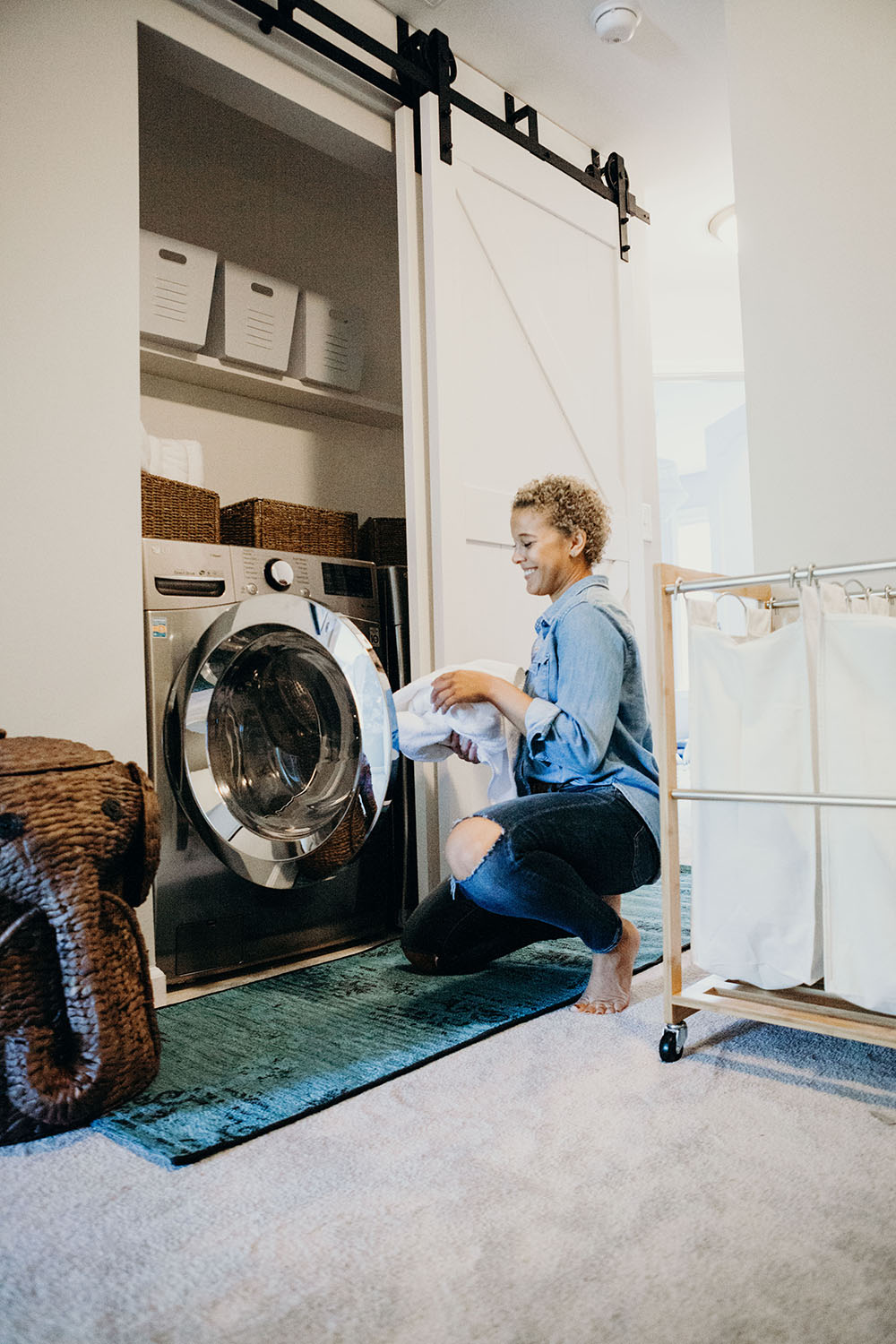 A woman kneeling to add clothes inside a front load washing machine.