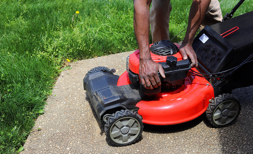 A person preparing a lawnmower for blade removal.