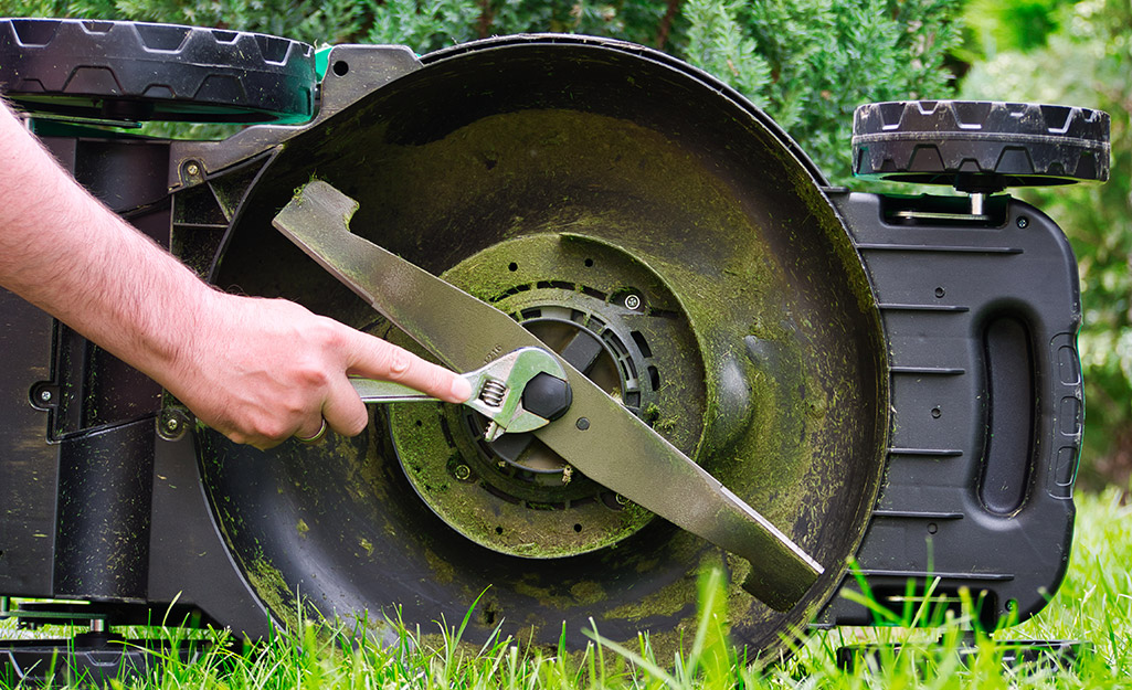 A person tightening a lawn mower blade.
