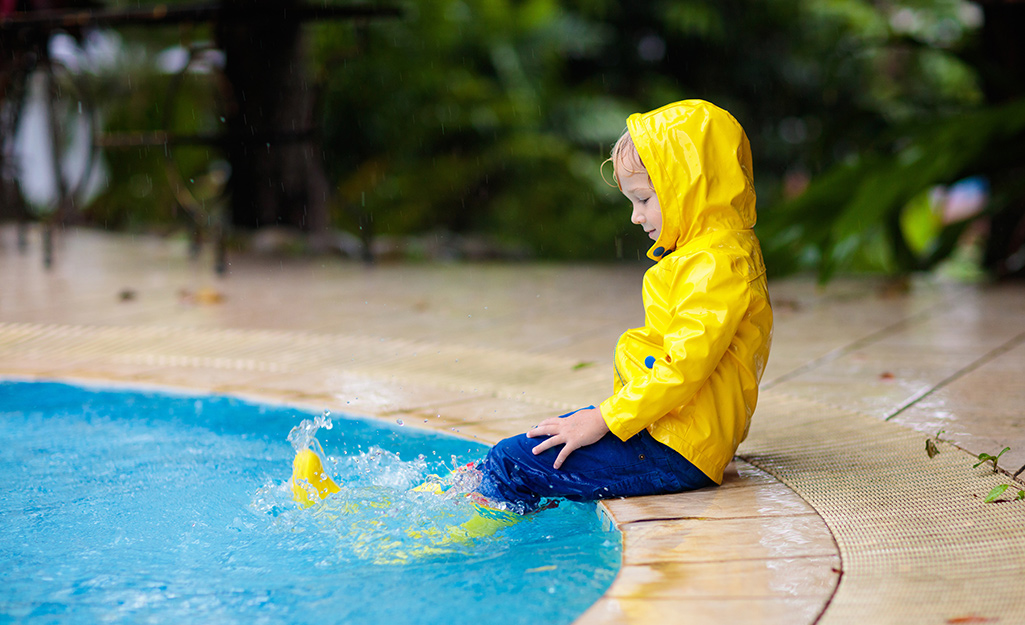 A child in rain gear sitting at the edge of a pool.