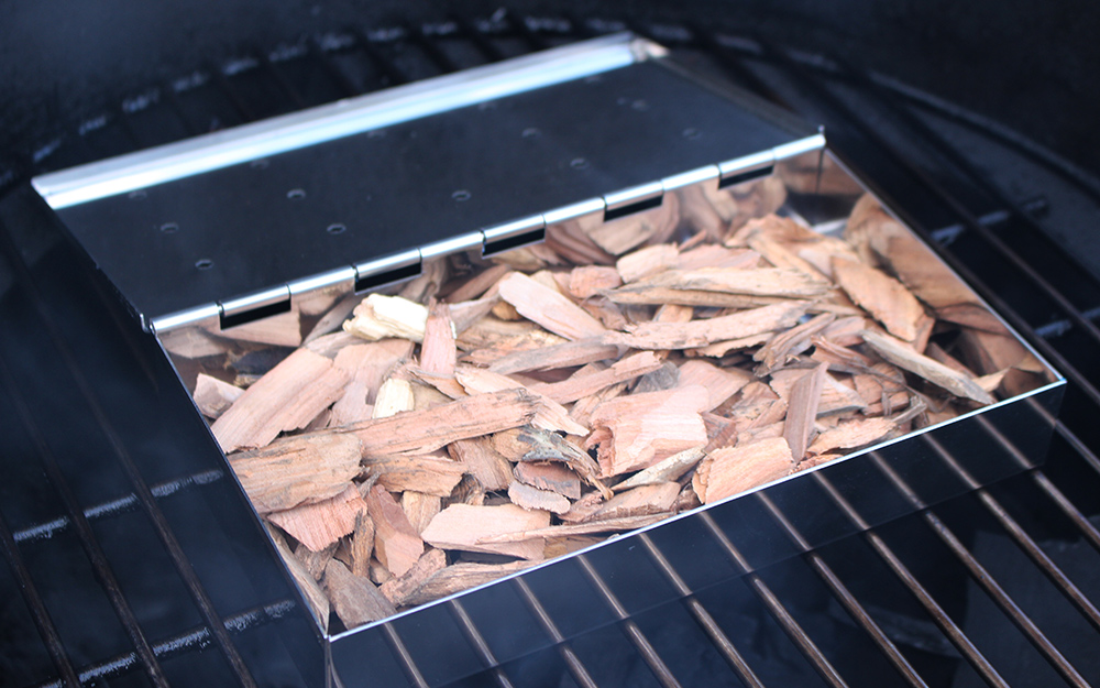 A tray of wood chips prepares a smoker for cooking.