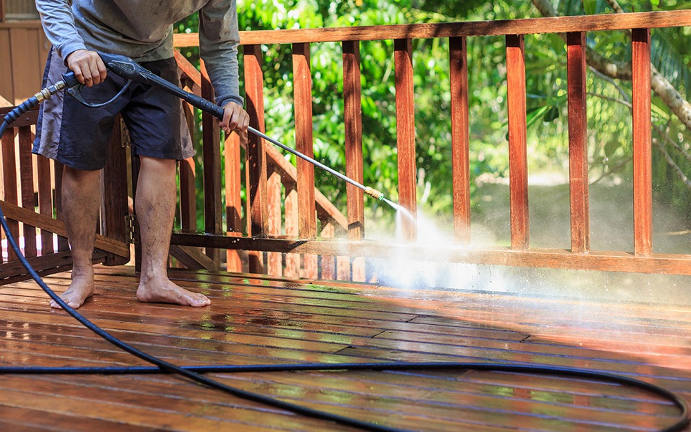 A person washes a deck with a sprayer.