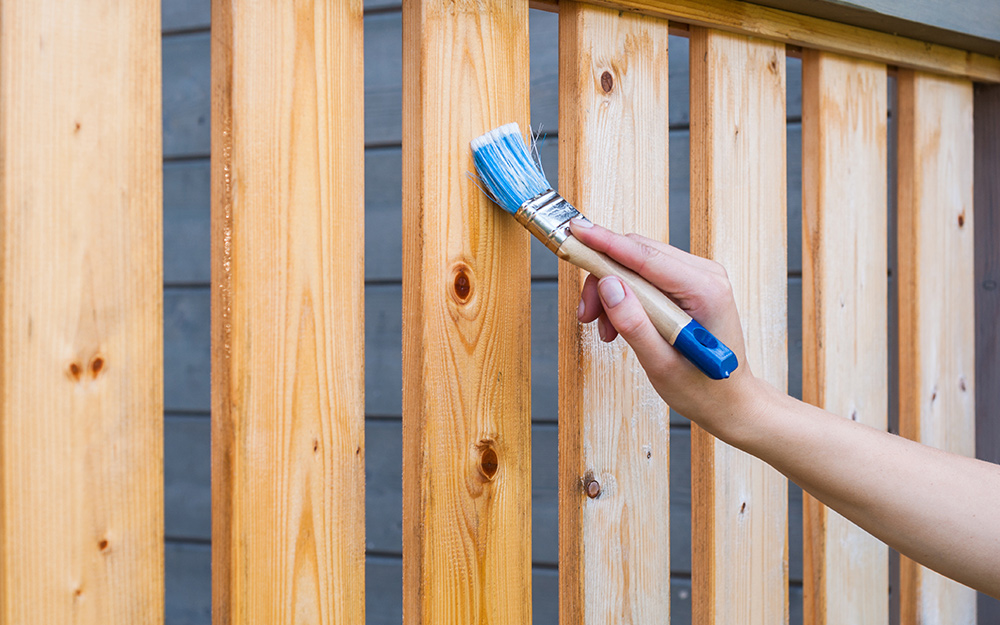 A person stains the balusters of a deck with a brush.