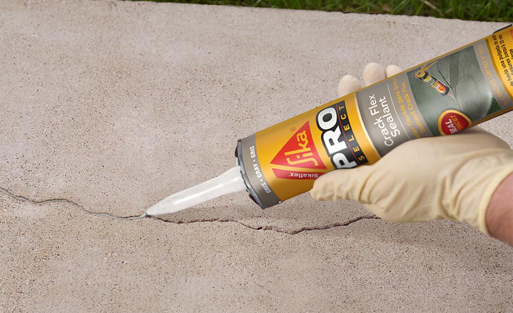 Một người bôi chất trám bít vào vết nứt trên bê tông.
