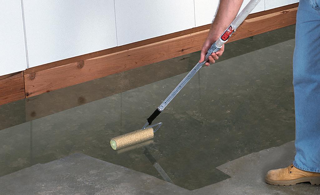 Một người sử dụng con lăn để thi công chất trám kín lên sàn bê tông.