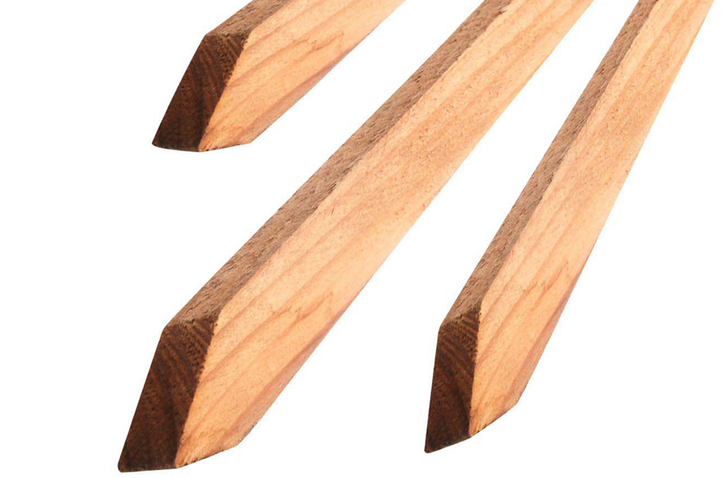 Up close view of wood stakes on white background.