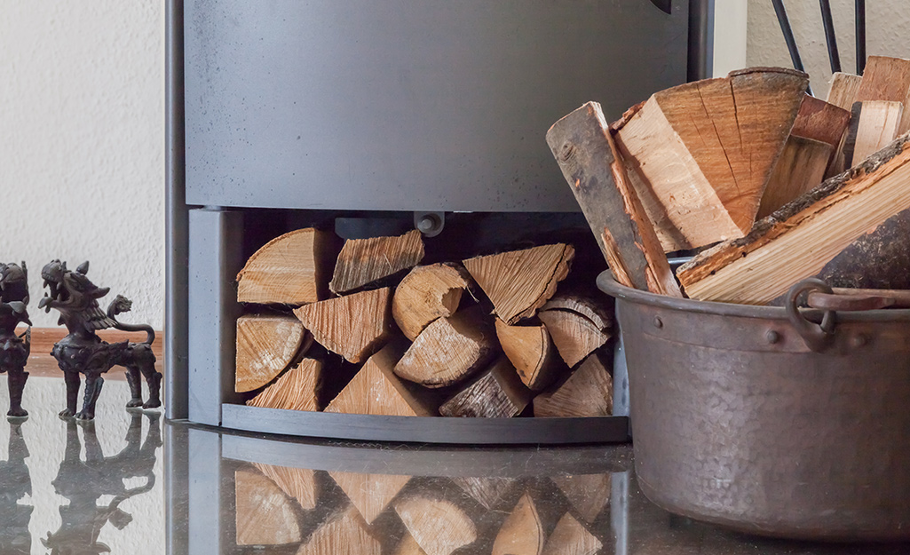 Stacks of firewood placed into a bucket in front of a fireplace.