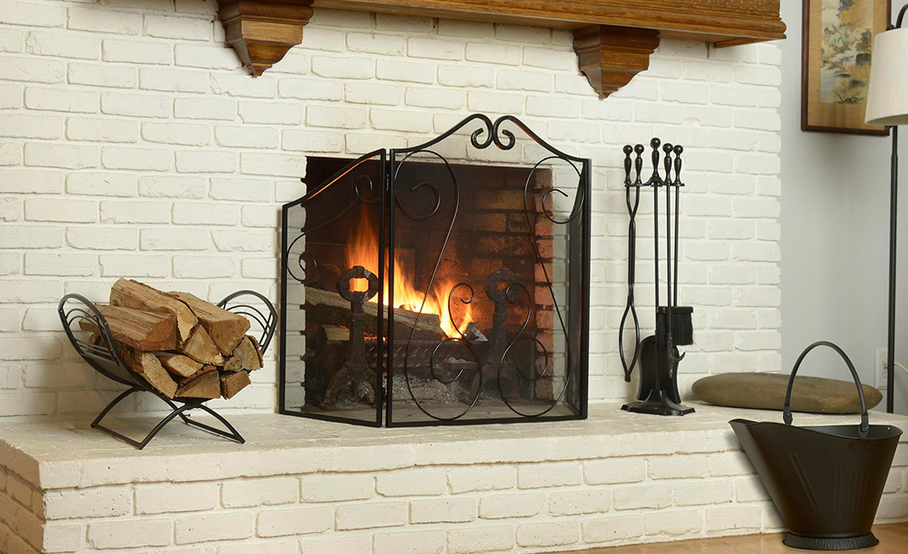 A wood-burning fireplace surrounded by wrought iron hearth accessories.