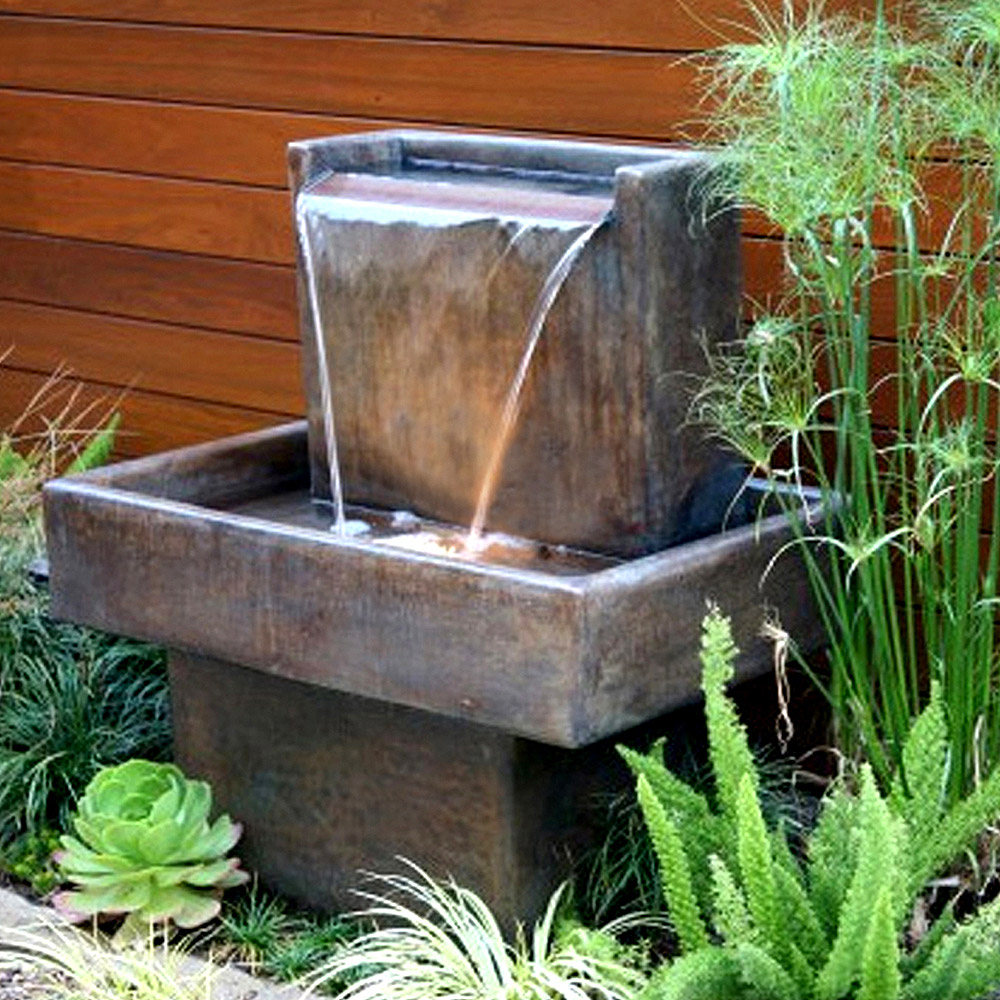 Water fountain surrounded by green plants against a redwood wall.