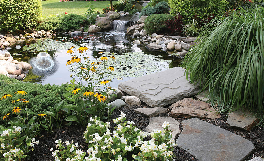 A backyard pond and waterfall surrounded by river rocks and flagstone.