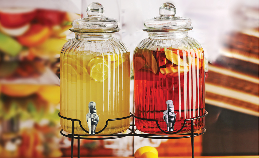 Glass beverage dispensers filled with lemonade and fruit punch.